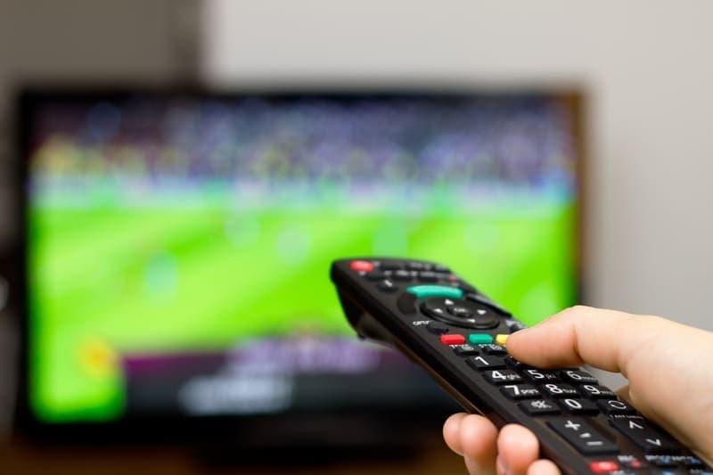 テレビのリモコンとテレビ。内容はサッカー